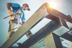 Wood Construction Works. Caucasian Worker on the Wooden Roof Construction Stock Image