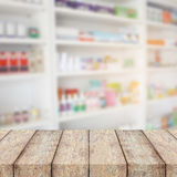 Wood counter with blur shelves of drug in the pharmacy Royalty Free Stock Image