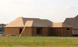 Wood Covered Frame of a Suburban Home Under Construction. Back View of the Exterior of a Wood Covered Frame skeleton of a Suburban Home under construction stock photos