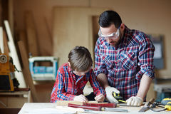 Wood craft. Carpenter and his son working with wooden planks Stock Images