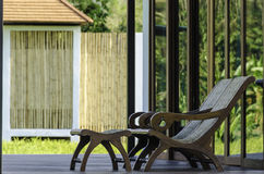Wood craft easy chair on wood terrace in green environment. With exotic house in background Royalty Free Stock Images
