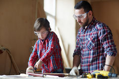 Wood craft. Father and son woodcrafting in workshop Stock Image