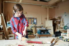 Wood crafting. Boy with wood-chisel carving wooden plank Stock Photo