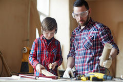 Wood creativity. Man and little boy carving wooden plank Stock Image