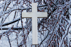 Wood cross hanging on ice covered tree branches Stock Photo