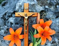 Crucifix in front of rock with orange flowers royalty free stock images