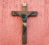 Wood crucifix on a pink background Royalty Free Stock Image