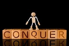 """Wood cube block with word """"CONQUER"""" and Wooden Stick Figure standing on Black Background. Conquering fear and success concept royalty free stock images"""