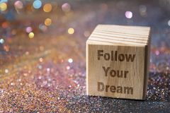 Follow your dream text on cube. Wood Cube with Follow your dream text on glitter royalty free stock image