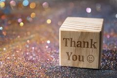 Thank you text on cube. Wood Cube with Thank you text on glitter Royalty Free Stock Photos