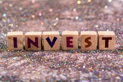 Invest word. Wood Cubes Invest word on glitter background Royalty Free Stock Photo