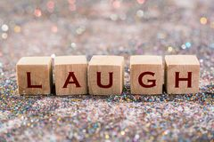 Laugh word. Wood Cubes Laugh word on glitter background Stock Photography