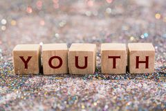 Youth word. Wood Cubes Youth word on glitter background royalty free stock photos