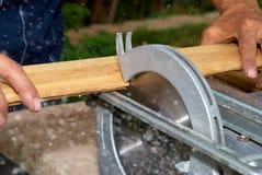 Wood cutting. Man cuts wooden board with circular saw Royalty Free Stock Photo