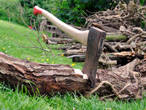 Wood Cutting - Axe Stuck in a Tree Log on Grass. Wood Cutting - Lumberjack's axe stuck in a tree log on green grass with a pile of firewood in the background Royalty Free Stock Image