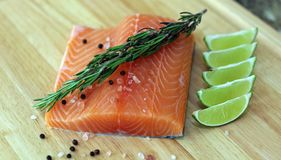 Wood cutting board in kitchen table with fresh red salmon fish salt pepper and lime ready to cook. Fresh cooking elements with healthy food for chef ready to Royalty Free Stock Photos
