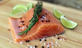 Wood cutting board in kitchen table with fresh red salmon fish salt pepper and lime ready to cook. Fresh cooking elements with healthy food for chef ready to Stock Images