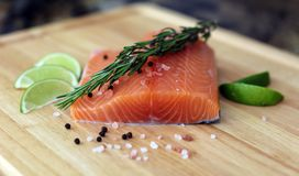 Wood cutting board in kitchen table with fresh red salmon fish salt pepper and lime ready to cook. Fresh cooking elements with healthy food for chef ready to Royalty Free Stock Photography