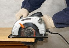 Wood cutting with circular saw. The worker cuts the wood with circular saw Stock Image
