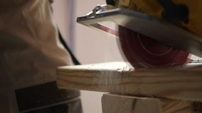 Wood cutting by circular saw. Construction site. stock video footage