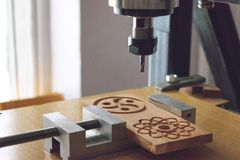 Wood cutting machine 3D wood cnc router. CNC milling machine carving a wooden part blank. Cutter controlled by computer while he. Is carving wood, drill, action royalty free stock images