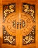 Wood dörr med drakar och svandesign Arkivbilder
