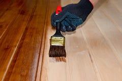 Wood dörryttersida för målning med en borste och målarfärg i svarta handskar Arkivfoto