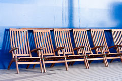 Wood Deck Chairs by a Blue Wall Stock Photography