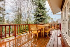 Wood deck with furniture and grey house. Royalty Free Stock Photography