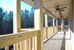 Wood Deck/Porch on House. A wood deck running along the back of a house, finished ceiling with fans and lights royalty free stock image