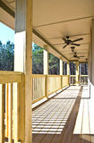 Wood Deck/Porch on House. A wood deck running along the back of a house, finished ceiling with fans and lights stock image
