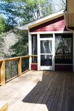 Wood Deck With Screened Porch. Wood deck with metal rails and screened porch on back of red house stock images