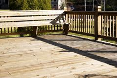 Wood Deck With Seating Area. A wood deck with bench area and a grassy yard in the background royalty free stock photo
