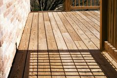 Wood Deck on Side of House. A wood deck running along the side of a house stock photo