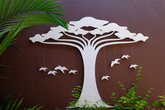 Wood decorate. White tree and birds cut from wood on brown wall and green tree Royalty Free Stock Photos