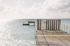 Wood dock constructed in the ocean on a calm sunny day. Empty wood dock / pier located in the ocean on a sunny day and calm sea Royalty Free Stock Photo