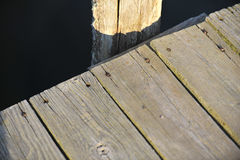 Wood dock and dark waters at sunset. Wood dock and pilings at sunset Royalty Free Stock Images