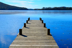 Wood dock extending over blue lake water Royalty Free Stock Images