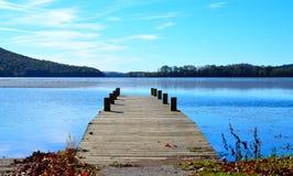 Wood dock extending over blue lake water. Wooden dock extending over scenic blue lake Stock Photography