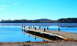 Wood dock extending over blue lake water Stock Image