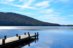 Wood dock extending over blue lake water Stock Photography