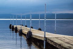 Wood dock on lake. At cloudy evening stock image