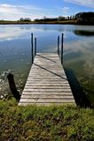Wood dock leads to the lake water. Dock leads into the still lake water on an early autumn morning Royalty Free Stock Photography