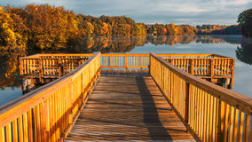 Wood Dock over pond or lake in fall autumn in Connecticut USA. Orange and red fall foliage on bridge in Connecticut USA Stock Photo