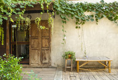 Wood door and bamboo bench with green plant Stock Photos