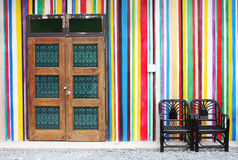 Wood door and black chair on colorful wall Stock Photography