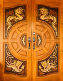 Wood door with dragons and swans design Stock Images
