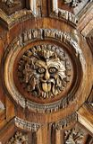 Wood Door Face La Valenciana Guanajuato. Detail of a comic carved face with the tongue out in the wood door of La Valenciana church, Guanajuato, mexican colonial Royalty Free Stock Photo