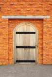 Wood door on orange brick wall Royalty Free Stock Photos