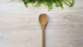 Wood drejare för Wood sked på vit wood bakgrund Arkivfoton